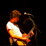 Guitarist playing electric guitar onstage.